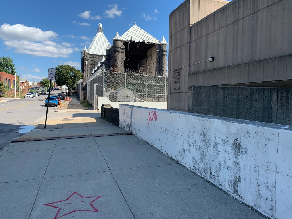 View down the street at the Baltimore City Jail being demolished. In the foreground on the sidewalk is a red star with a name of a victim of police violence.