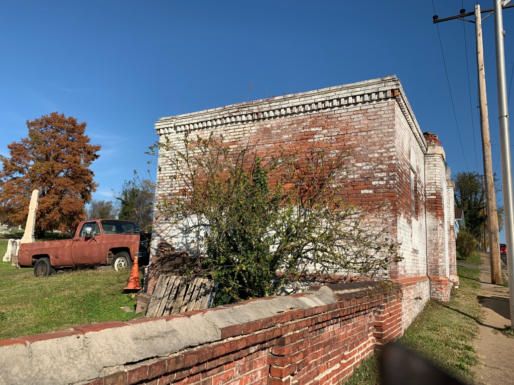 A small old brick building is set against a blue sky. A low brick wall extends along the sidewalk. On the other side is a cemetery.