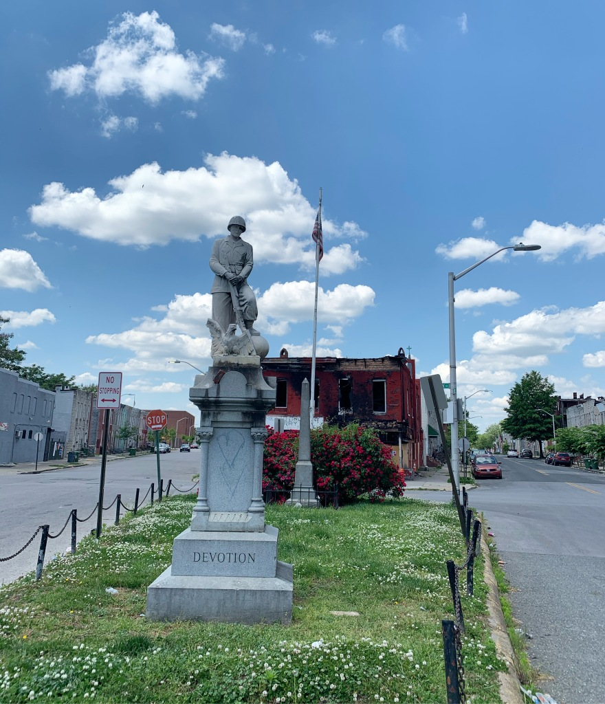 Monument with a soldier and eagle on a post that reads DEVOTION against a blue sky with puffy clouds. Streets are on either side, and a burned-out red brick building is in the background.