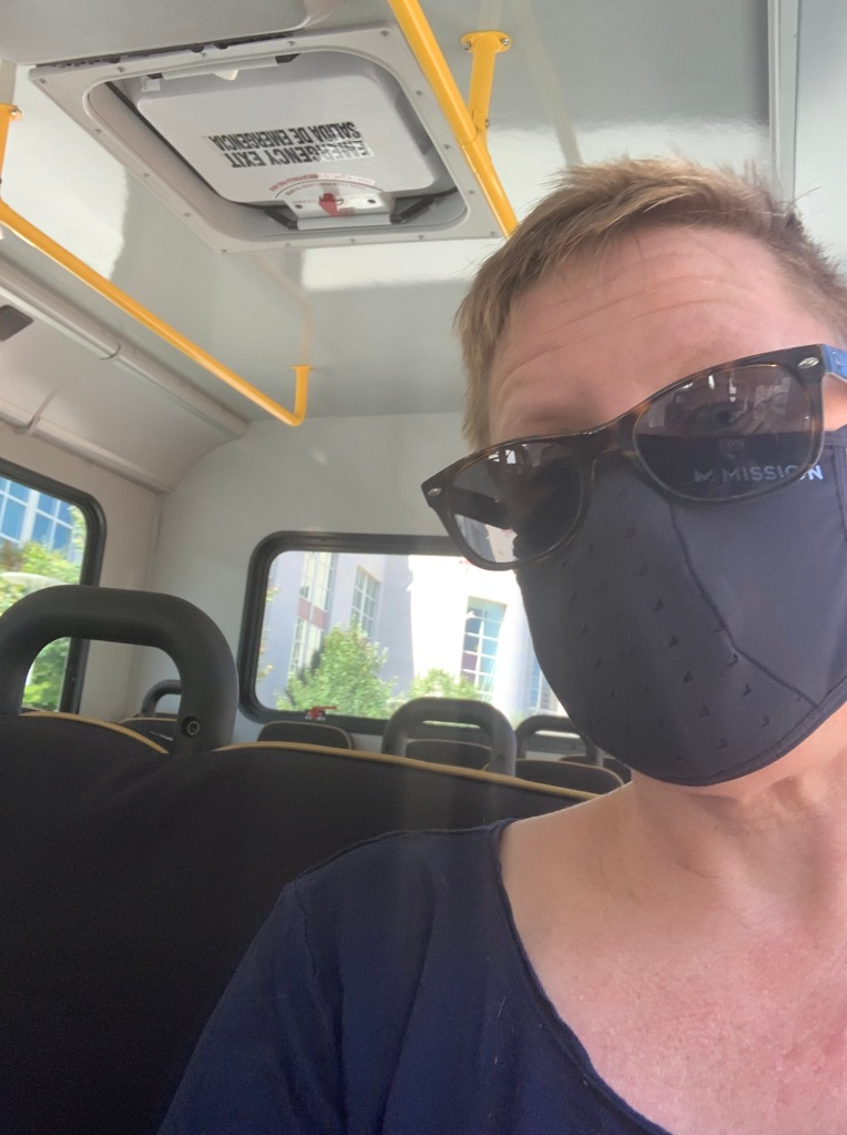 Selfie of a white woman with short blond hair on a shuttle bus. She is wearing a blue facemask over her nose and mouth and sunglasses.