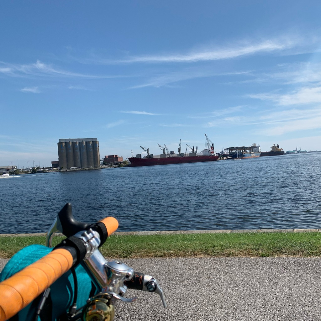 Bike handlebars in the foreground against a background of blue sky with wispy white clouds and darker blue water.